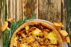 Традиционный шведский пирог - киш при грибы, сыр и травы лисички украшенные с свежим розмариновым маслом на кухонном столе стоковая фотография rf