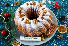 Традиционный fruitcake для рождества украшенный с напудренным сахаром и гайками, изюминками стоковые фото