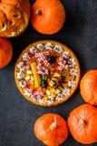 Традиция хеллоуина Пирог тыквы и тыква с страшной стороной на черном copyspace взгляд сверху предпосылки Стоковое фото RF