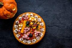 Традиция хеллоуина Пирог тыквы и тыква с страшной стороной на черном copyspace взгляд сверху предпосылки Стоковые Изображения RF