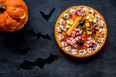 Традиция хеллоуина Пирог тыквы, тыква с высекаенной стороной и летучие мыши на черном взгляд сверху предпосылки Стоковое Фото