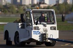 Трактор буксировки хвостом вперед в авиапорте Стоковые Изображения RF