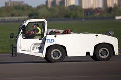 Трактор буксировки хвостом вперед в авиапорте Стоковые Фото