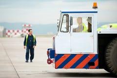Трактор буксировки хвостом вперед ГУЖА в авиапорте Стоковые Изображения RF