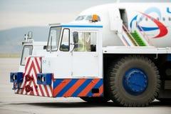 Трактор буксировки хвостом вперед ГУЖА в авиапорте Стоковое Изображение