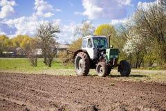 Трактор вспахивает землю Стоковое Изображение