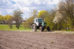 Трактор вспахивает землю Стоковая Фотография