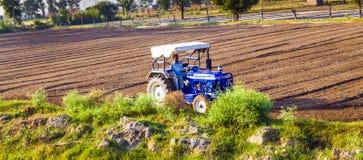 Трактор вспахивает поле стоковая фотография rf
