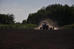 Трактор вспахивает поле Стоковое Фото