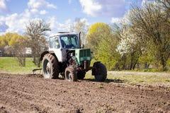 Трактор вспахивает участок земли Стоковое Изображение RF