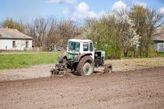 Трактор вспахивает участок земли Стоковое фото RF
