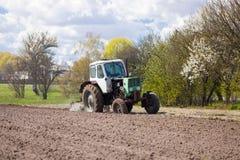Трактор вспахивает участок земли Стоковые Изображения