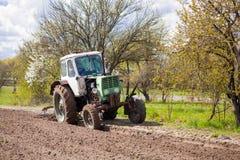 Трактор вспахивает участок земли Стоковая Фотография RF