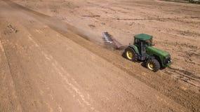 трактор вспахивая взгляд сверху поля, воздушное фотографирование с трутнем стоковое фото