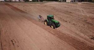 трактор вспахивая взгляд сверху поля, воздушное фотографирование с трутнем сток-видео