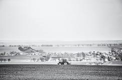 Трактор вспахивая на пшеничном поле, бесцветном Стоковые Изображения