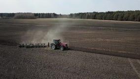 Трактор вспахивая поле, взгляд от трутня видеоматериал