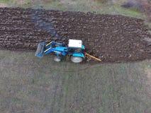 Трактор вспахивая сад Вспахивать почву в саде Стоковые Фотографии RF