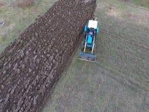 Трактор вспахивая сад Вспахивать почву в саде Стоковое Фото
