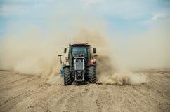 Трактор вспахивая сухое сельскохозяйственное угодье на осени Стоковое фото RF