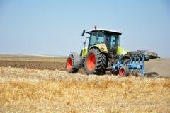 Трактор вспахивая, трактор в поле стоковая фотография rf