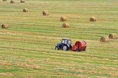 Трактор вытягивает круглый Baler на заднем плане поля Стоковое Изображение RF