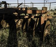 Трактор вытянул плужок с заржаветыми лезвиями в конце вверх по детали Стоковая Фотография RF