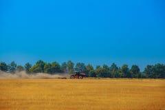 Трактор летнего дня вытягивает плужок на склоняя поле пшеницы Стоковая Фотография