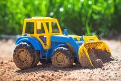 Трактор игрушки в песке Стоковые Изображения