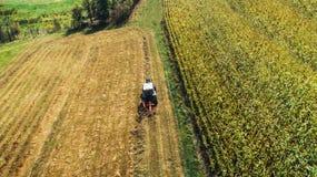 Трактор используя роторное машинное оборудование граблей, жать детали Собирать сена и продукция пшеницы стоковое фото rf