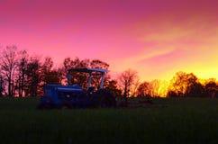 Трактор и линия деревьев на заходе солнца против неба Стоковые Фото