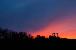 Трактор и линия деревьев на заходе солнца против неба Стоковые Изображения