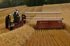 Трактор и swather Джона Dere жать пшеницу Стоковое Изображение RF