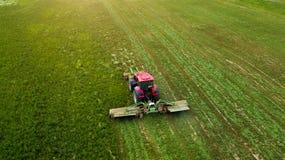 Трактор косит поле воздушного фотографирования с трутнем стоковая фотография