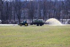 Трактор лить поле с жидкостным поземом для лучшей структуры поля Необходимо для лучшего сбора стоковые фотографии rf