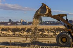 Трактор льет гравий от ведра стоковые изображения rf