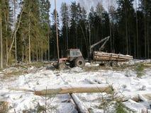 Трактор нагружая древесину стоковая фотография