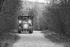Трактор на вымощенных ездах дороги со светами вокруг древесин, делая работу на местах после сумерек Monohrom стоковое фото