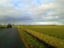 Трактор на дороге около поля весны Стоковые Фотографии RF