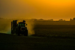 Трактор на поле во время захода солнца стоковые фотографии rf