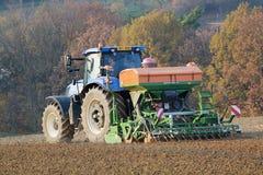 Трактор осеменяя урожаи Стоковые Изображения