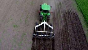 Трактор отпускает землю в поле Воздушный отснятый видеоматериал Летать над трактором в поле видеоматериал