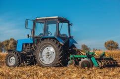 Трактор после полудня осени едет и вытягивает плужок, вспахивает поле после сбора хлопьев - мозоли Стоковое Изображение RF