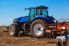 Трактор после полудня осени едет и вытягивает плужок, вспахивает поле после сбора хлопьев - мозоли Стоковое Изображение