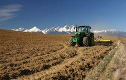 Трактор под горами стоковая фотография rf