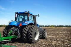 Трактор при плужок работая в поле Стоковое фото RF