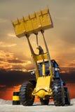 Трактор работая в карьере на заходе солнца Стоковое Изображение RF