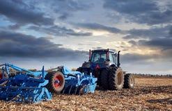 Трактор работая в поле на заходе солнца Стоковое Изображение