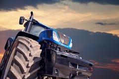 Трактор работая на предпосылке захода солнца Стоковая Фотография RF