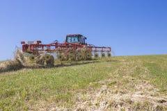 Трактор сгребая сено над склоняемой землей стоковое фото